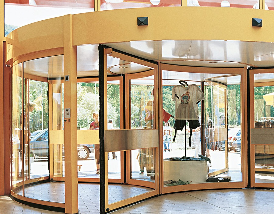 Glass revolving door with gold trim
